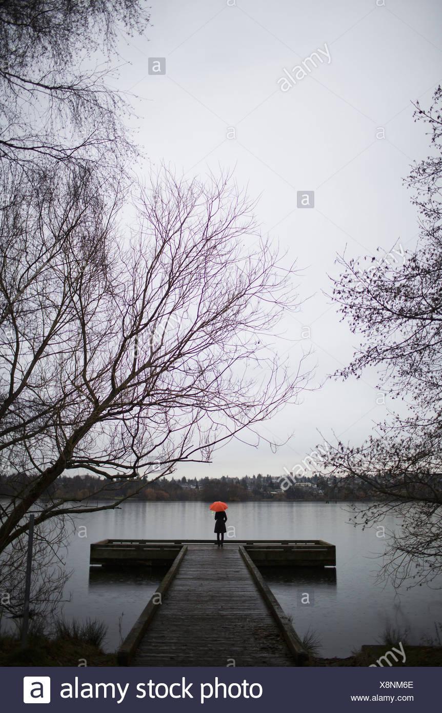 Eine Frau stand am Ende ein Dock mit einem orange Regenschirm an einem bewölkten grauen Tag in Seattle Stockbild