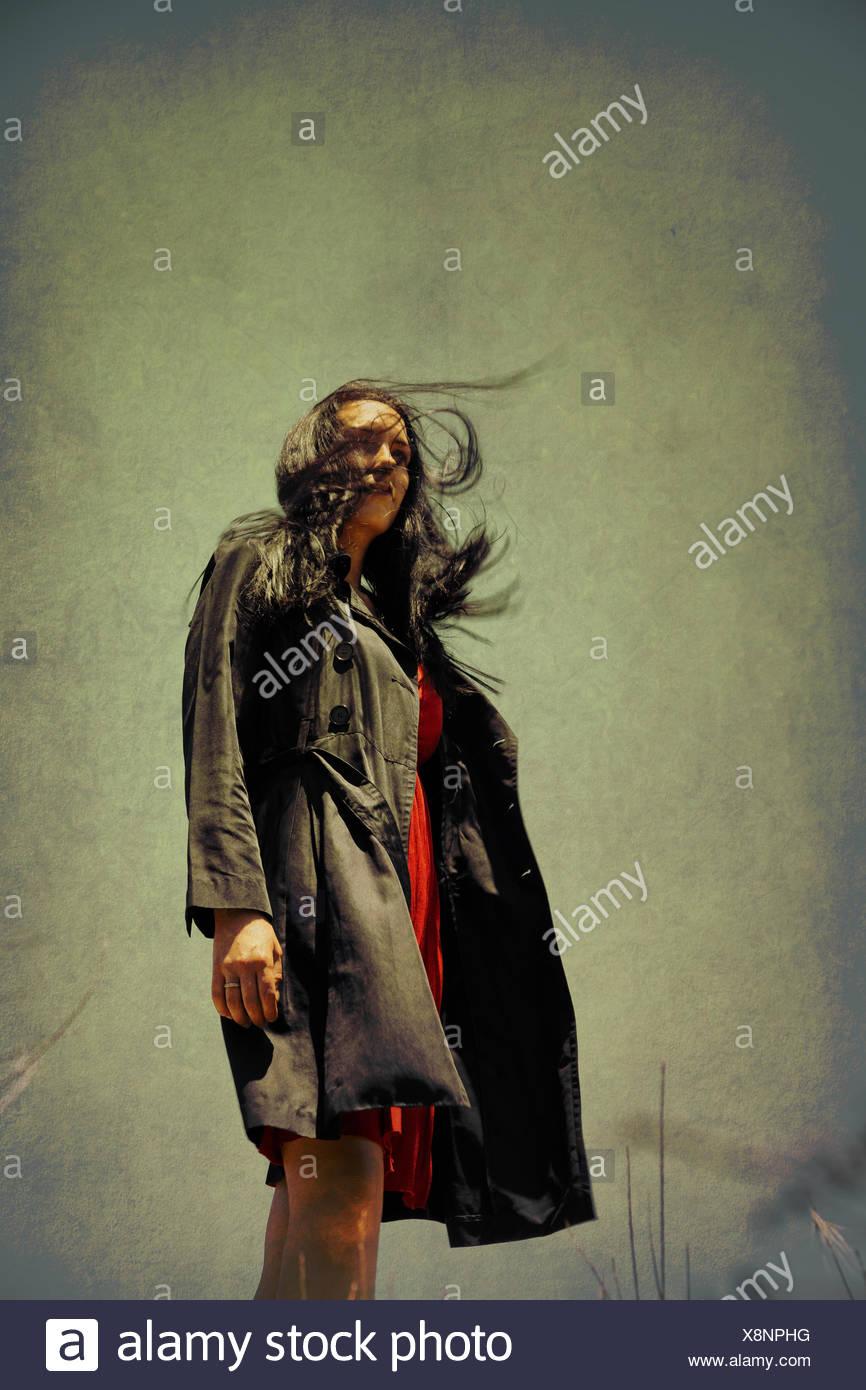 Windige Frau im schwarzen Mantel Stockfoto