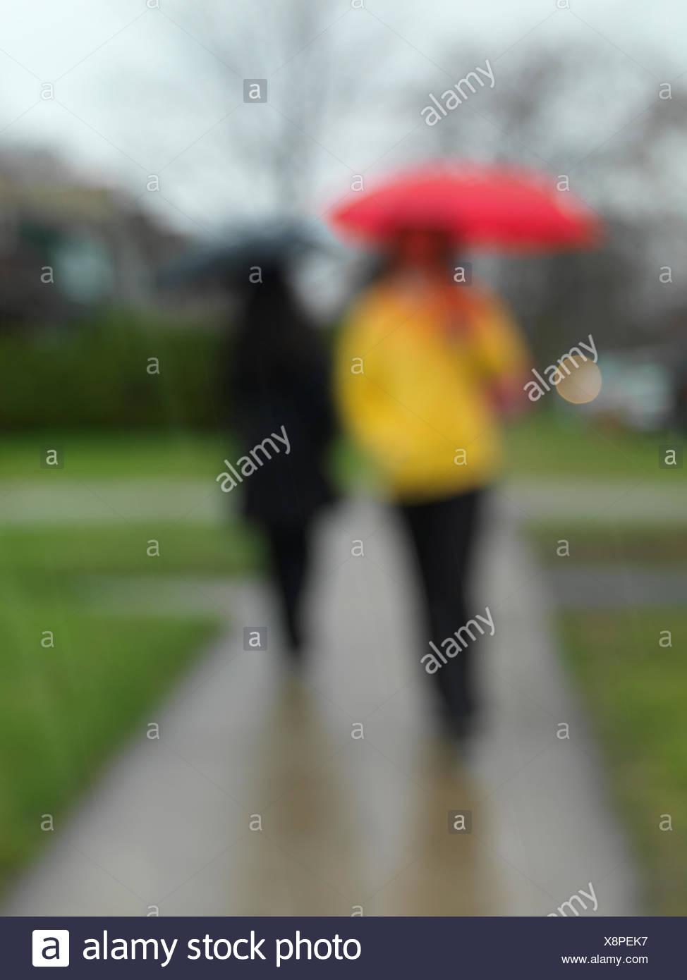 Menschen mit Regenschirmen auf einem Bürgersteig in der Regen verwischt Stockfoto