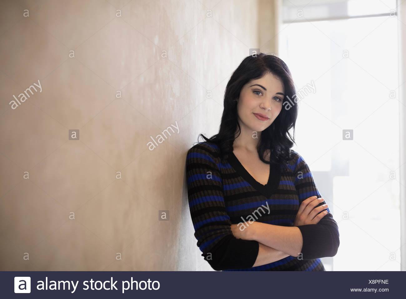 Porträt, selbstbewusste Frau mit Arme gekreuzten schiefen Wand Stockbild