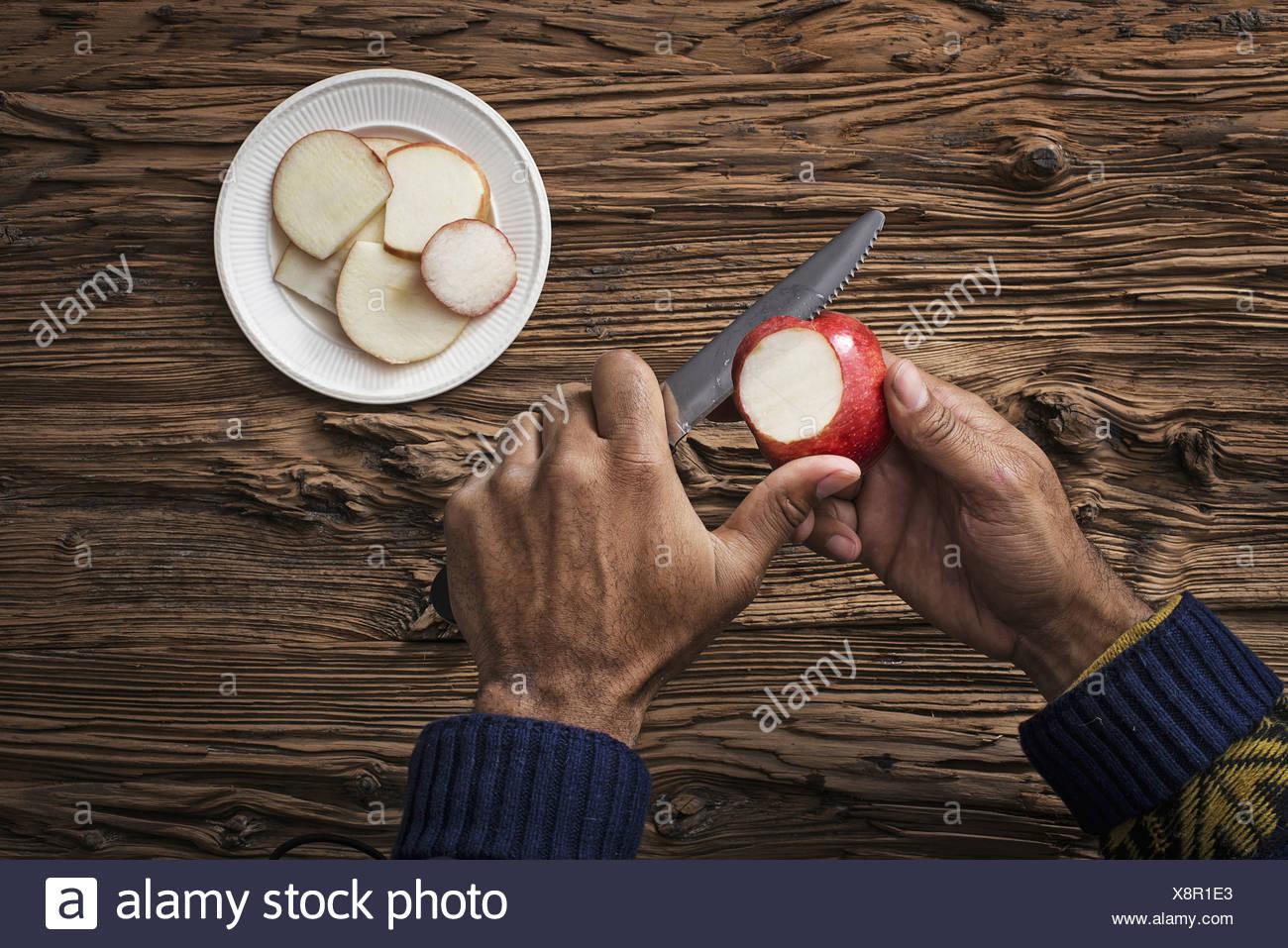 Eine Person hält und schneiden Abschnitte eines roten Apfels gehäutet Stockbild