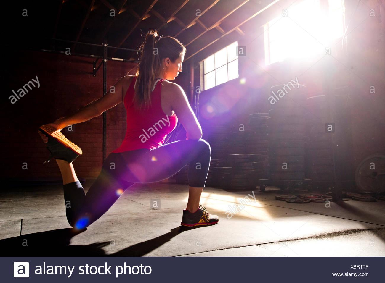 Eine Sportlerin erstreckt sich in einer Crossfit Gym. Stockbild