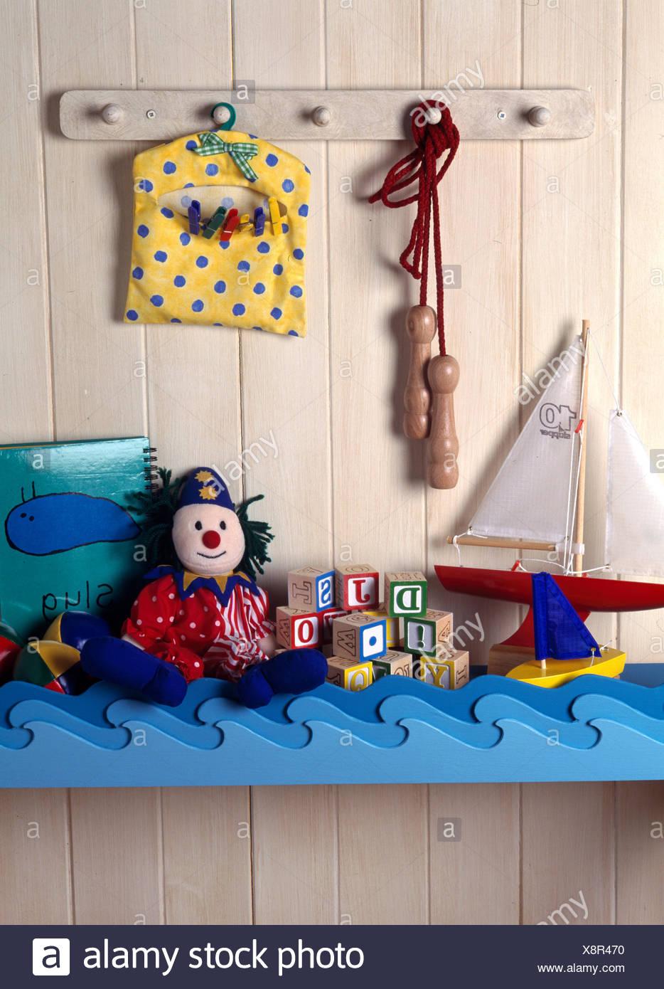 Spielzeug auf maritim eingerichteten Regal des Kindes auf der Zunge + roove Wand Stockfoto