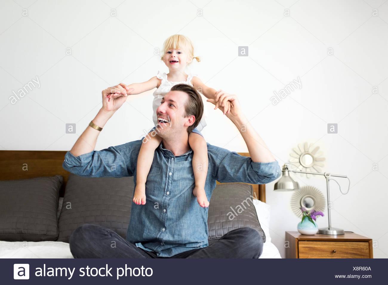 Porträt des Vaters mit Tochter (2-3) auf Schultern Stockbild