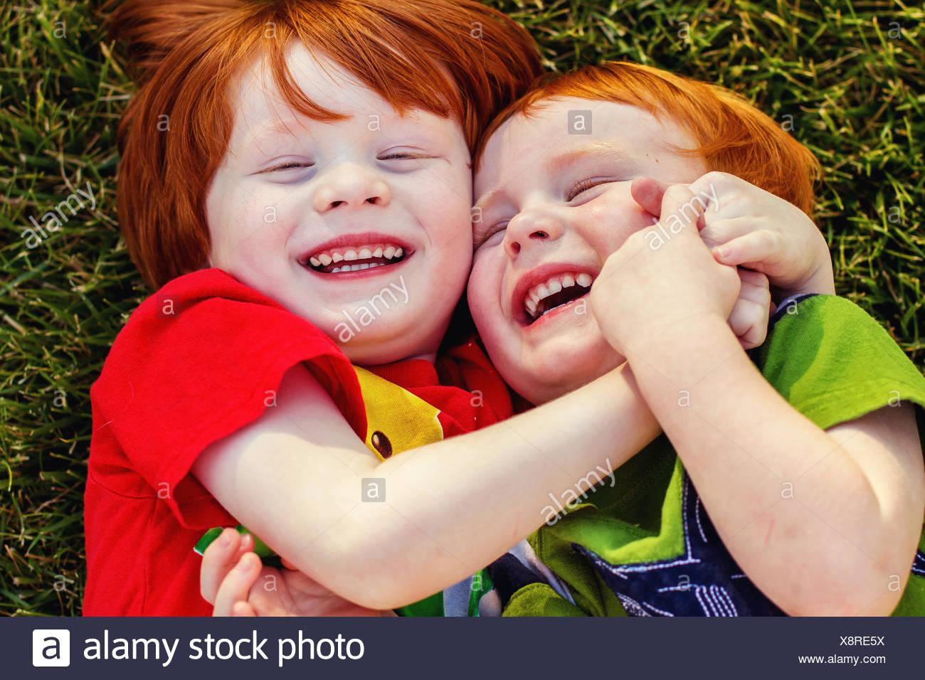 Zwei glückliche Jungs liegen auf Rasen vor Lachen Stockbild