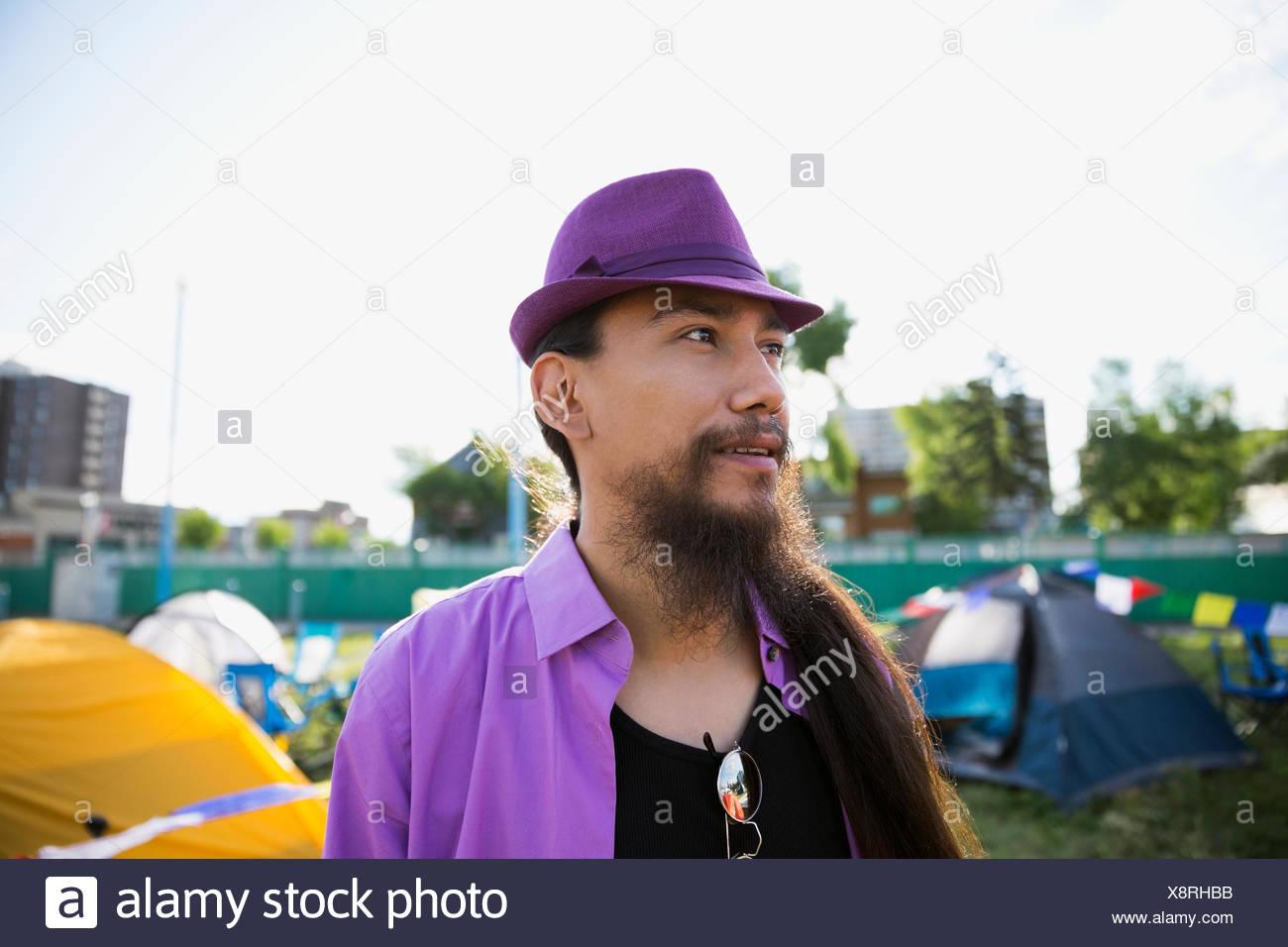 Junger Mann mit langen Haaren und Bart tragen lila Hut wegsehen bei Sommer-Musik-Festival-Campingplatz Stockbild