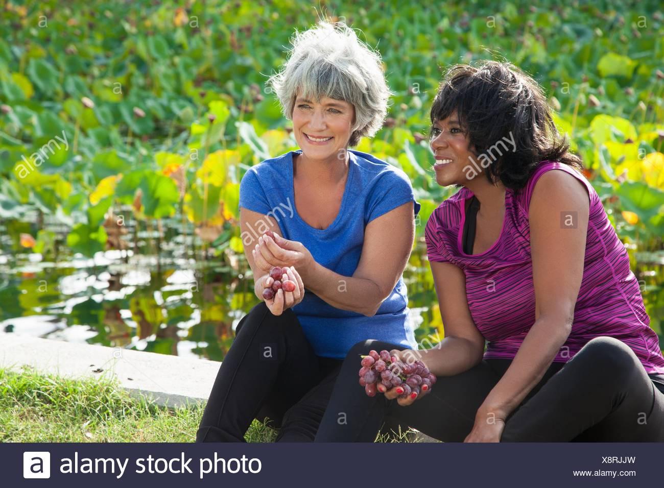 Reife Freundinnen sitzen im Park, essen Trauben Stockbild