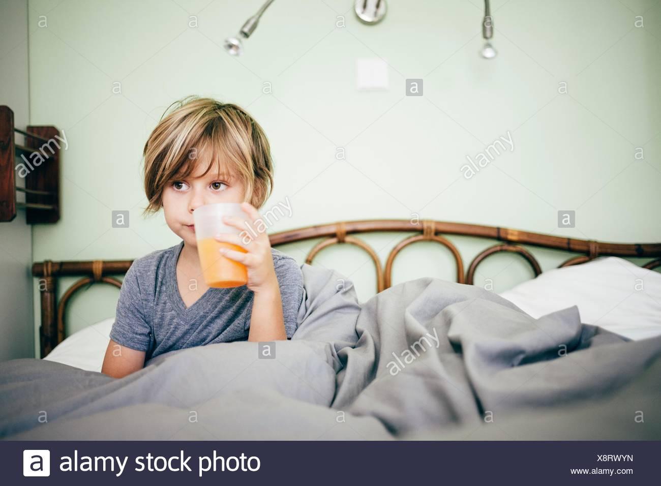 Junge sitzt im Bett trinken Becher Orangensaft, wegsehen, Bludenz, Vorarlberg, Österreich Stockfoto