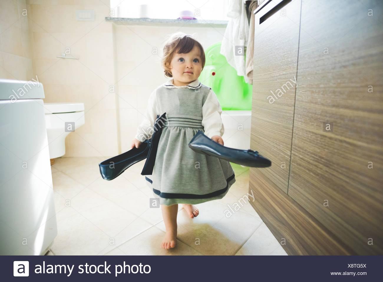 Weiblichen Kleinkind tragen Damenschuhe zu Hause Stockbild