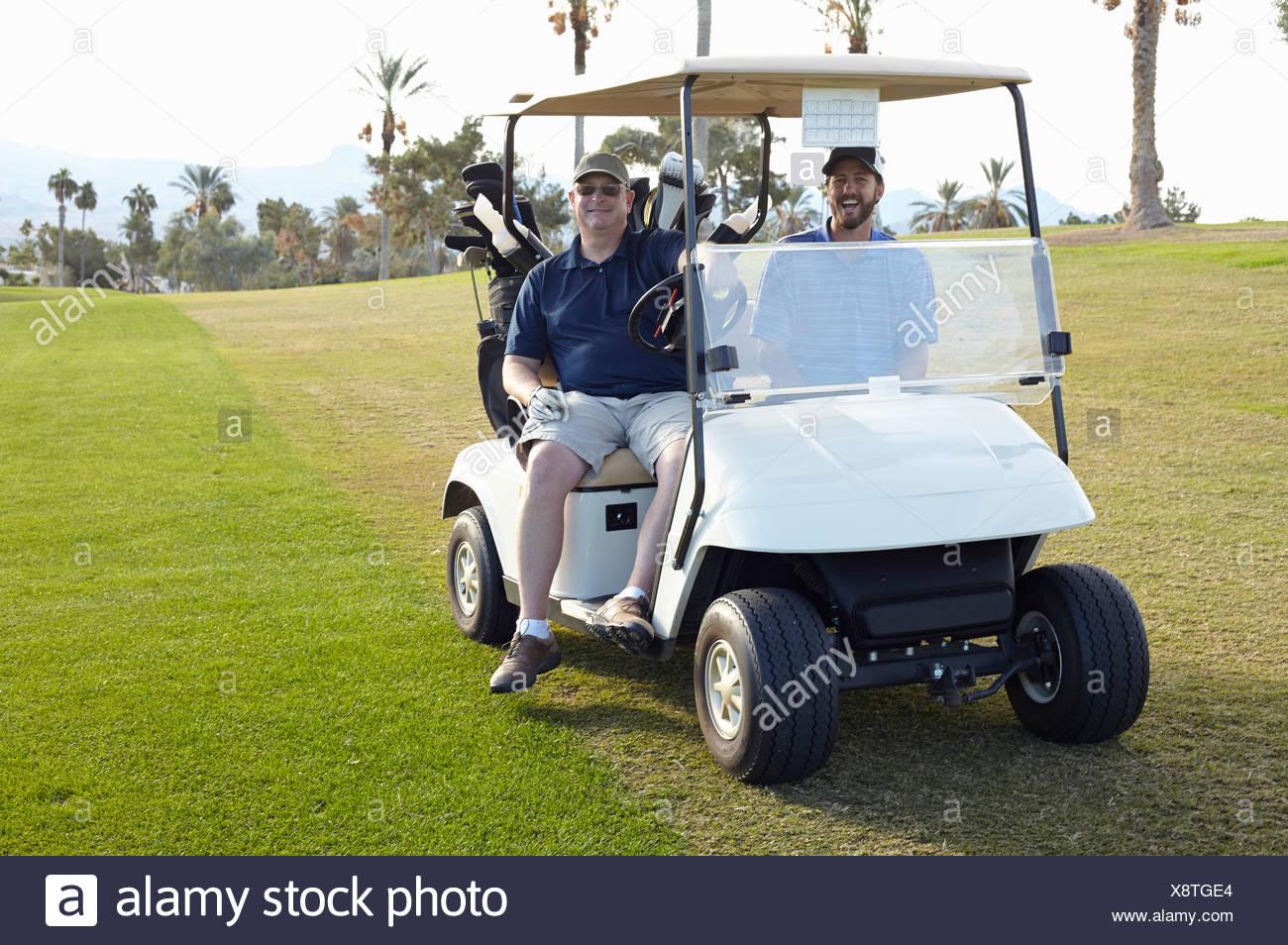 Porträt von zwei männlichen Golfer im Golfbuggy Stockbild
