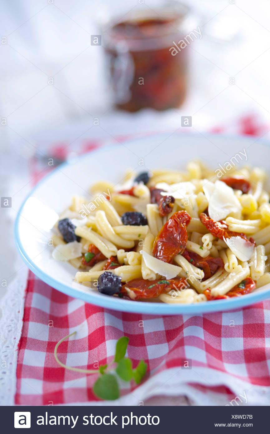Nudeln mit getrockneten Tomaten, Oliven und Parmesan-Käse Stockbild