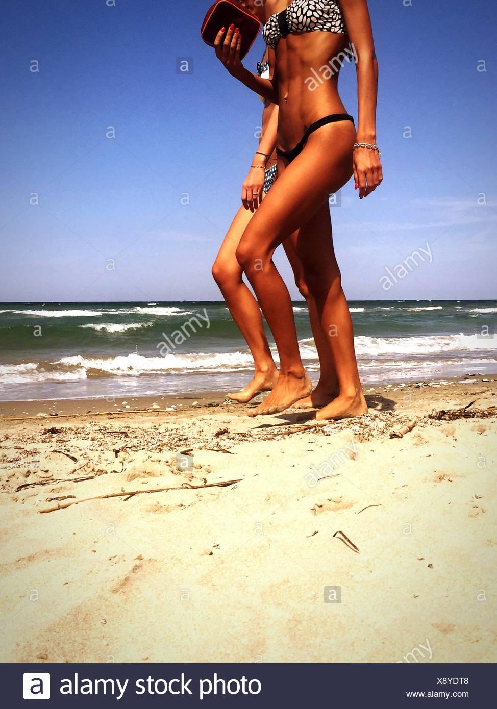 Zwei Frauen am Strand spazieren Stockbild