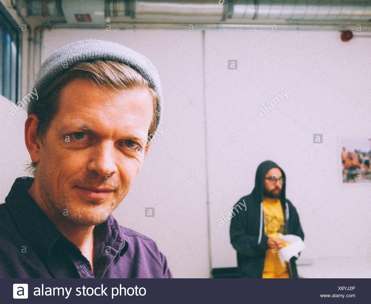 Porträt von zuversichtlich Geschäftsmann mit Kollegen im Hintergrund Stockfoto