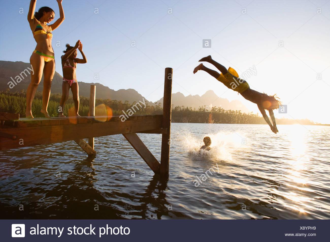 Vater und Sohn 8 10 in Badebekleidung tauchen ab Anlegestelle in See bei Sonnenuntergang Mutter und Tochter 7 9 jubelnden Objektiv flare Stockbild