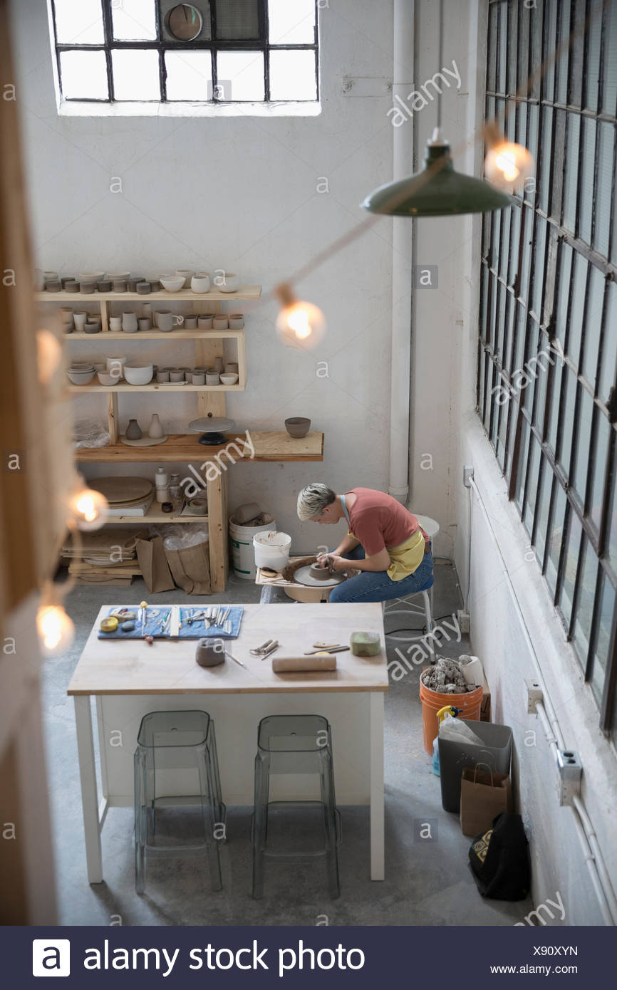 Anzeigen weibliche Töpferei mit Keramik Rad in art studio Erhöhte Stockbild