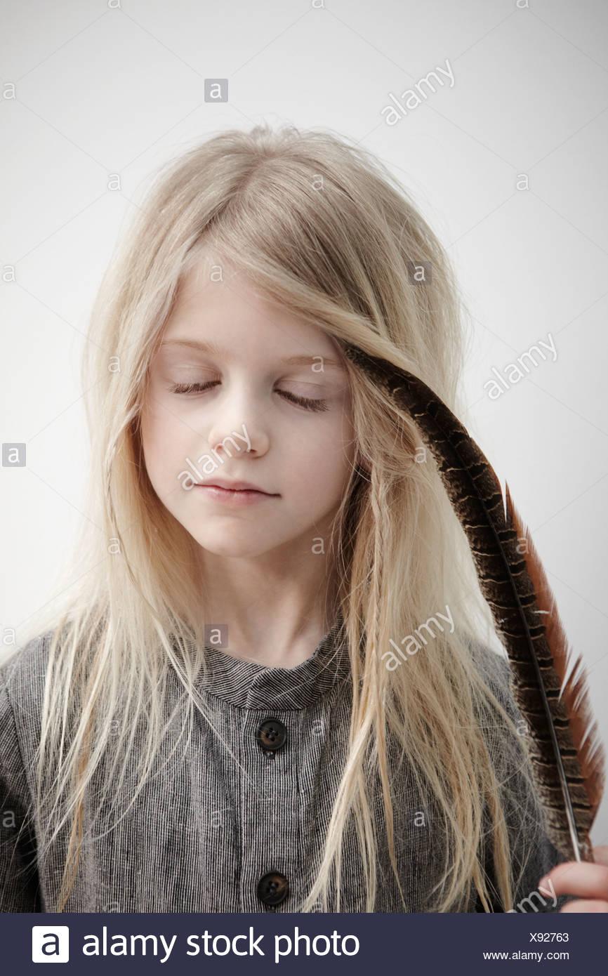 Porträt von Mädchen, die Feder, Augen geschlossen halten Stockbild