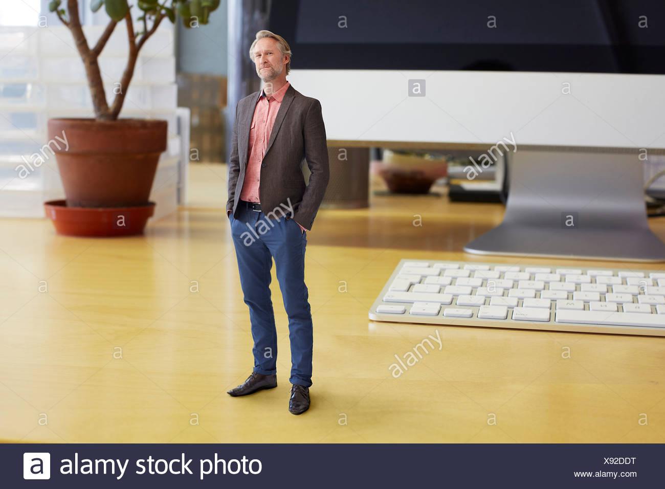 Reife Geschäftsmann auf übergroße Schreibtisch stehend Stockfoto