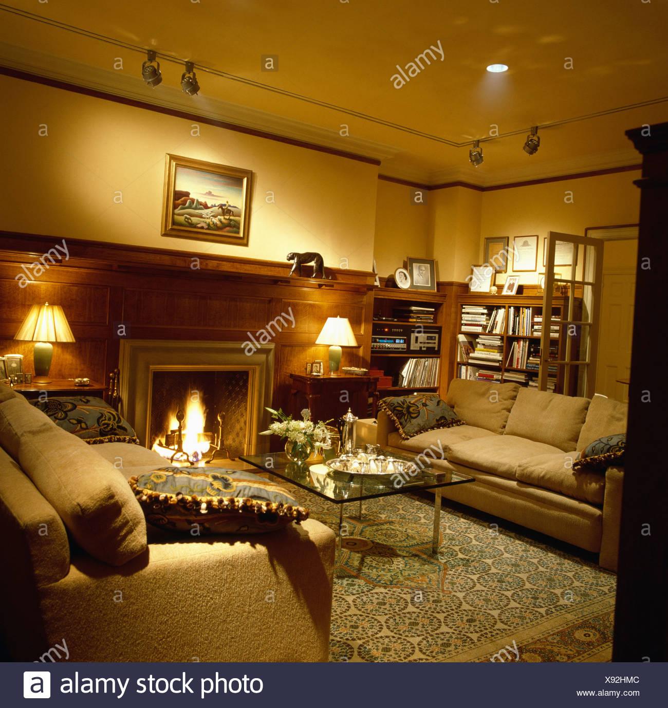 Gemütliches Wohnzimmer mit brennenden Lampen und beigefarbenen Sofas ...