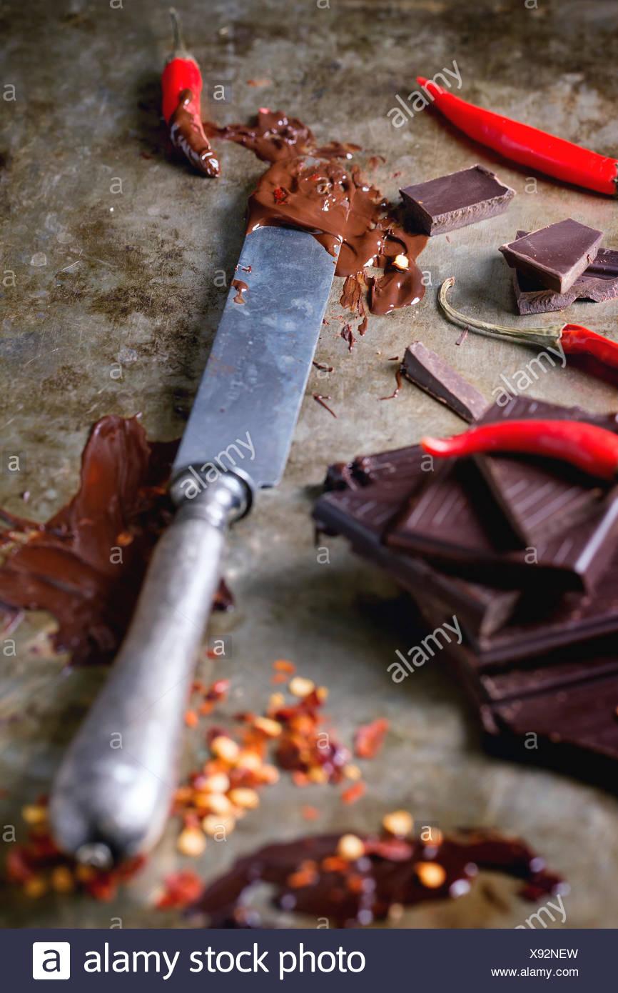 Hacken und schmelzen dunklen Schokolade mit frischen und trockenen roten hot Chili Peppers und Vintage Messer über alte Metall Hintergrund. Stockbild