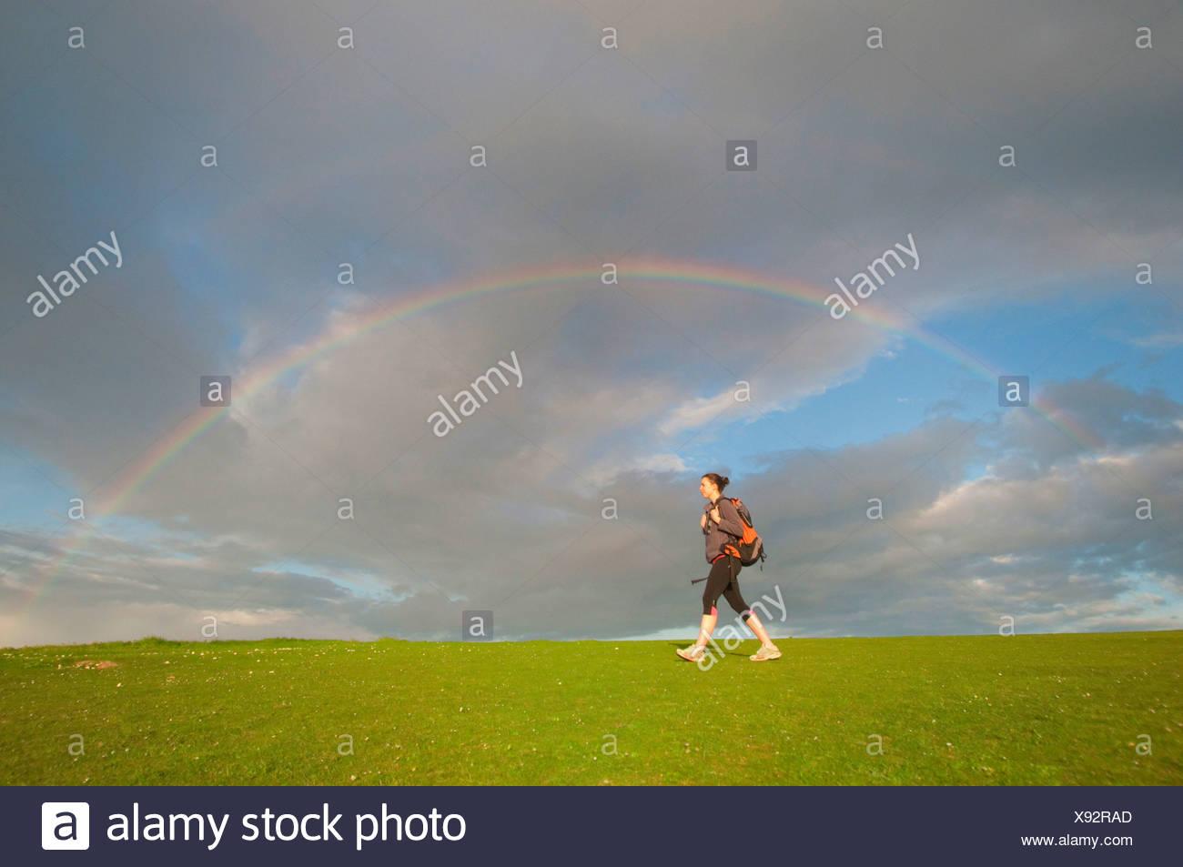 Junge weibliche Wanderer, Wandern unter Regenbogen Stockbild