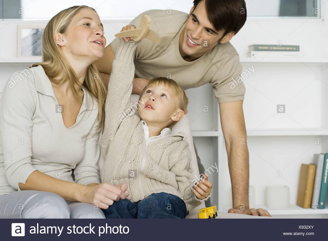 Kleiner Junge spielt mit Spielzeugflugzeug, Eltern beobachten Stockbild