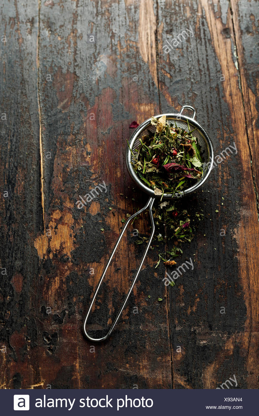 Tee-Stainer mit aromatischen Kräutertee auf Holztisch Hintergrund Stockbild