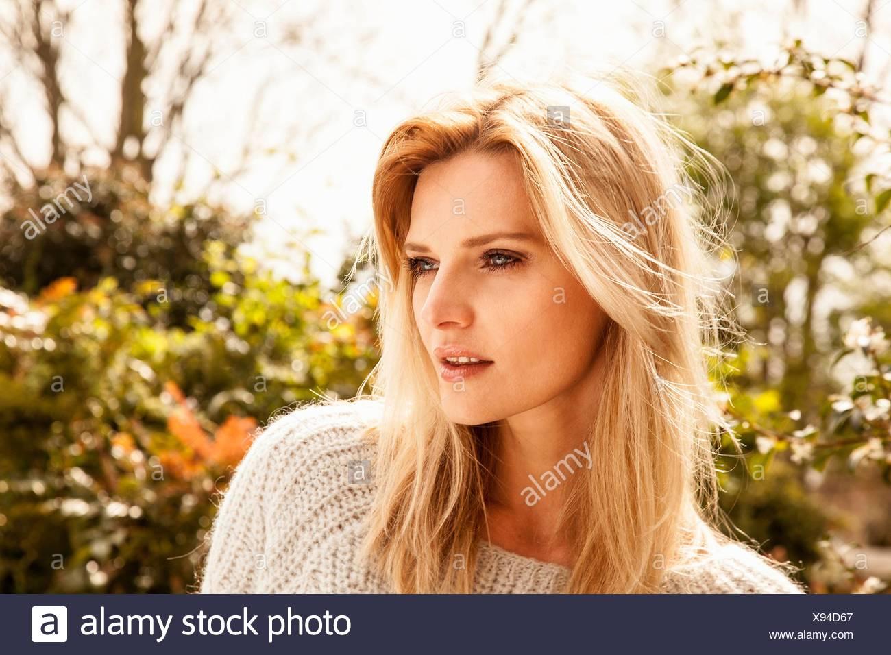 Schöne Mitte Erwachsene Frau mit langen blonden Haaren im Garten Stockbild