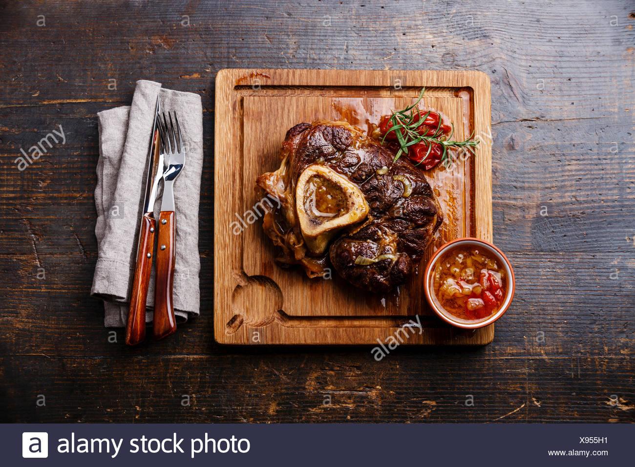 Ossobuco Kalbshaxe mit Tomaten auf dem Board auf hölzernen Hintergrund vorbereitet Stockbild