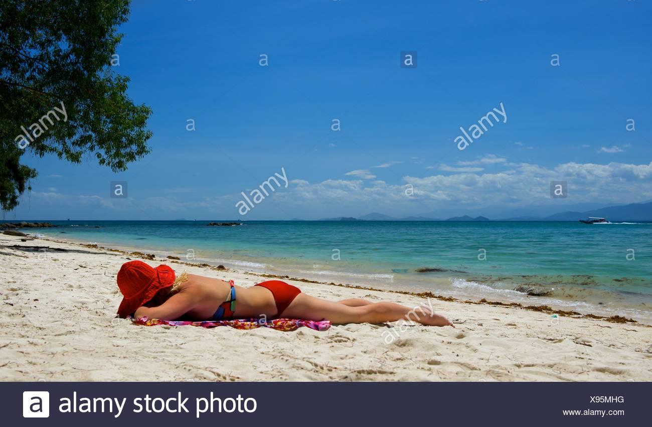 Frau, Sonnenbaden am Strand, Malaysia Stockbild