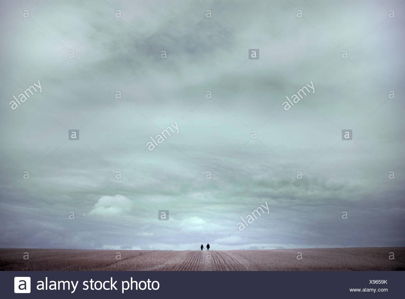 Zwei Menschen, die zu Fuß über Feld in Ferne Stockbild