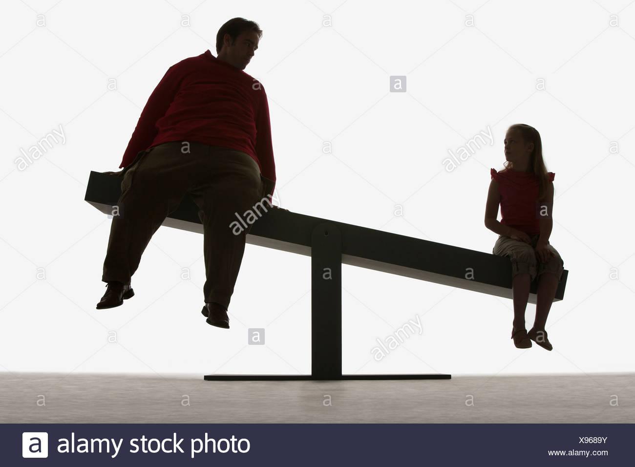 Mann und Mädchen sitzen an den Enden der ein Brett Stockbild