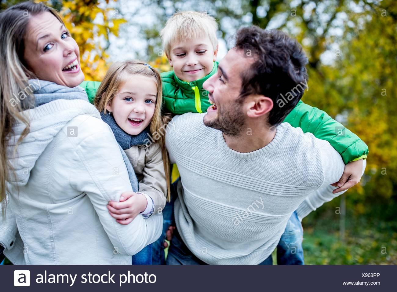 -MODELL VERÖFFENTLICHT. Eltern tragen ihre Kinder im Herbst, lachen. Stockfoto