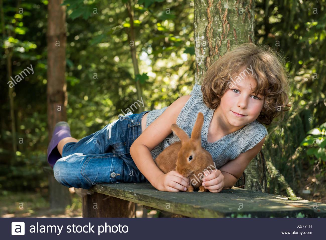 Junge (6-7) holding Hauskaninchen und liegend auf Bank im Wald Stockbild