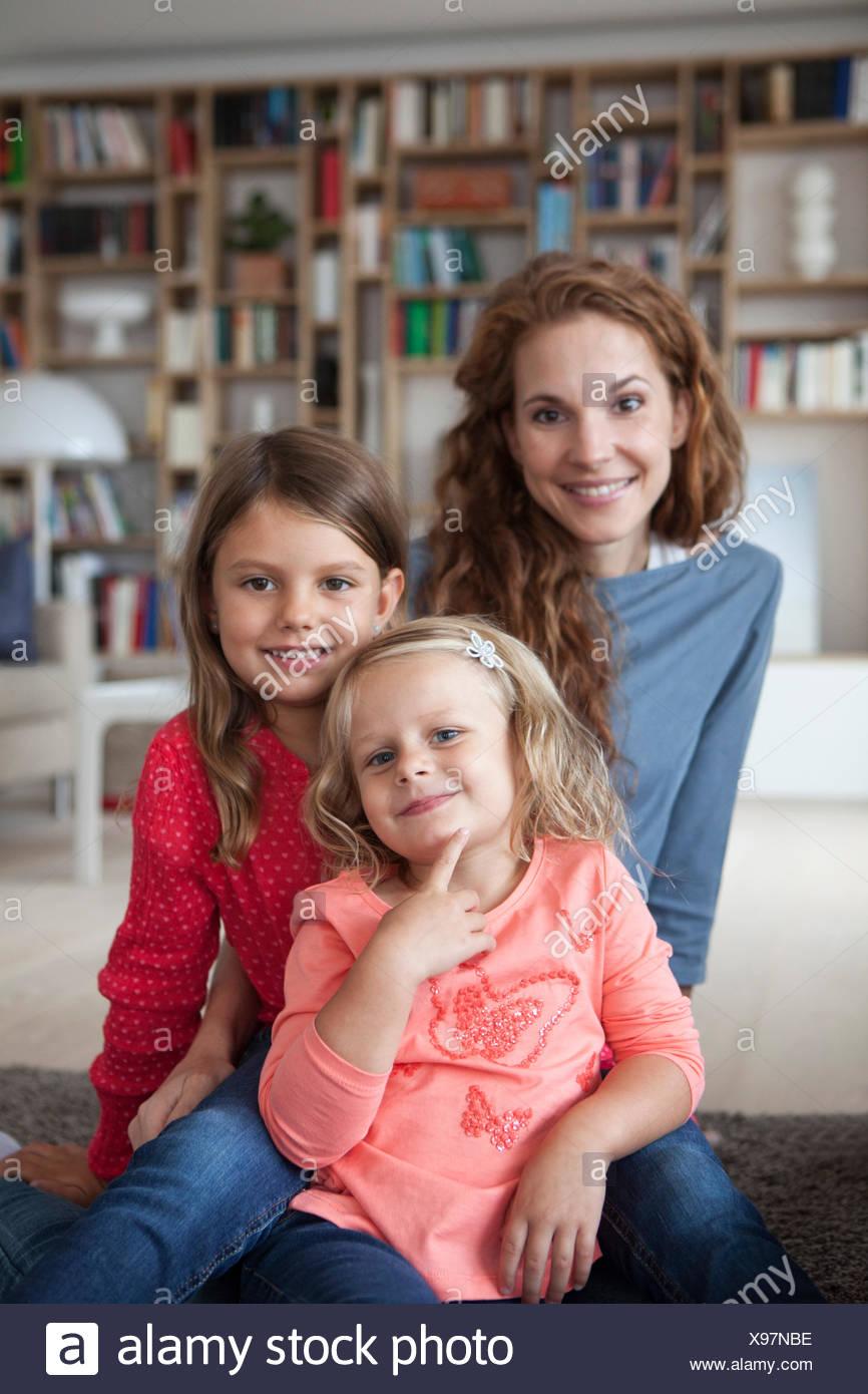 Porträt von zwei kleinen Schwestern und ihrer Mutter im Hintergrund sitzen auf dem Boden im Wohnzimmer Stockbild