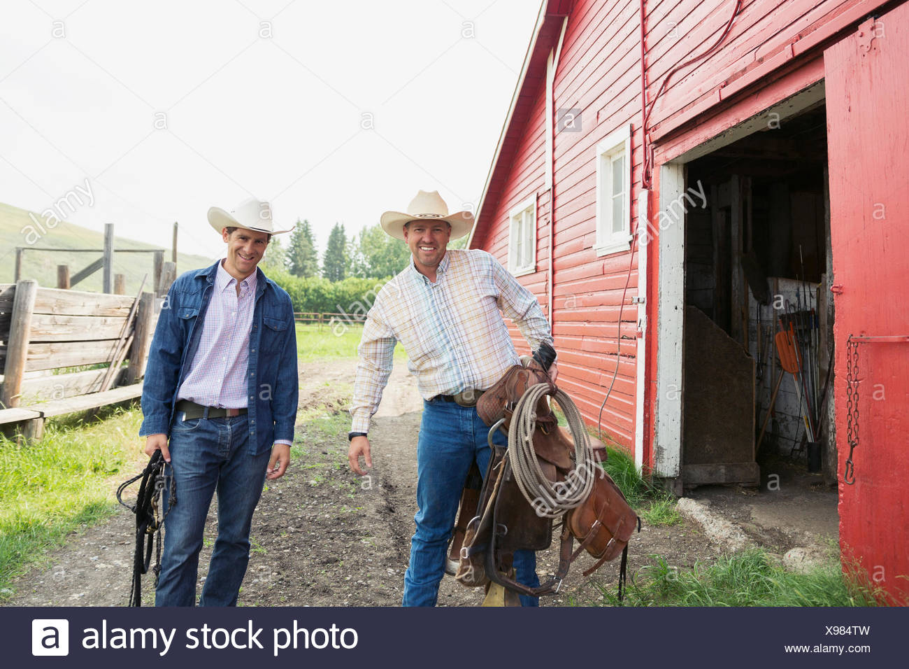 Viehzüchter mit Sattel und Zaumzeug außerhalb Scheune Stockbild