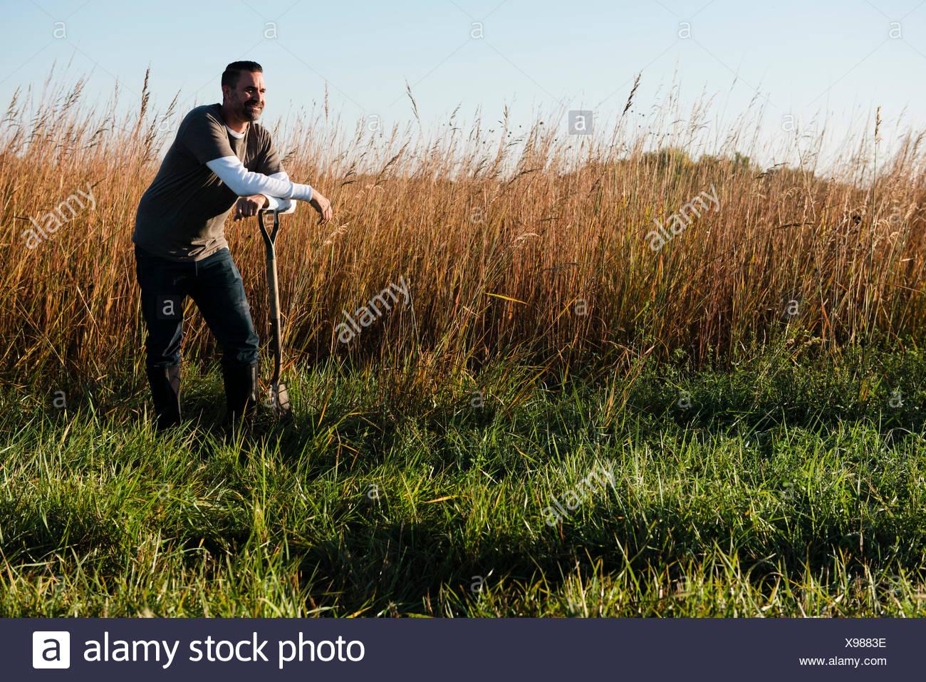 Porträt von Mitte erwachsenen männlichen Bauern stützte sich auf Spaten im Feld, Plattsburg, Missouri, USA Stockbild