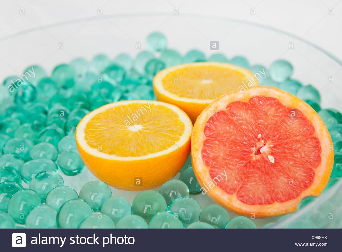 Halbierte Zitrusfrüchte mit Glasperlen Stockbild