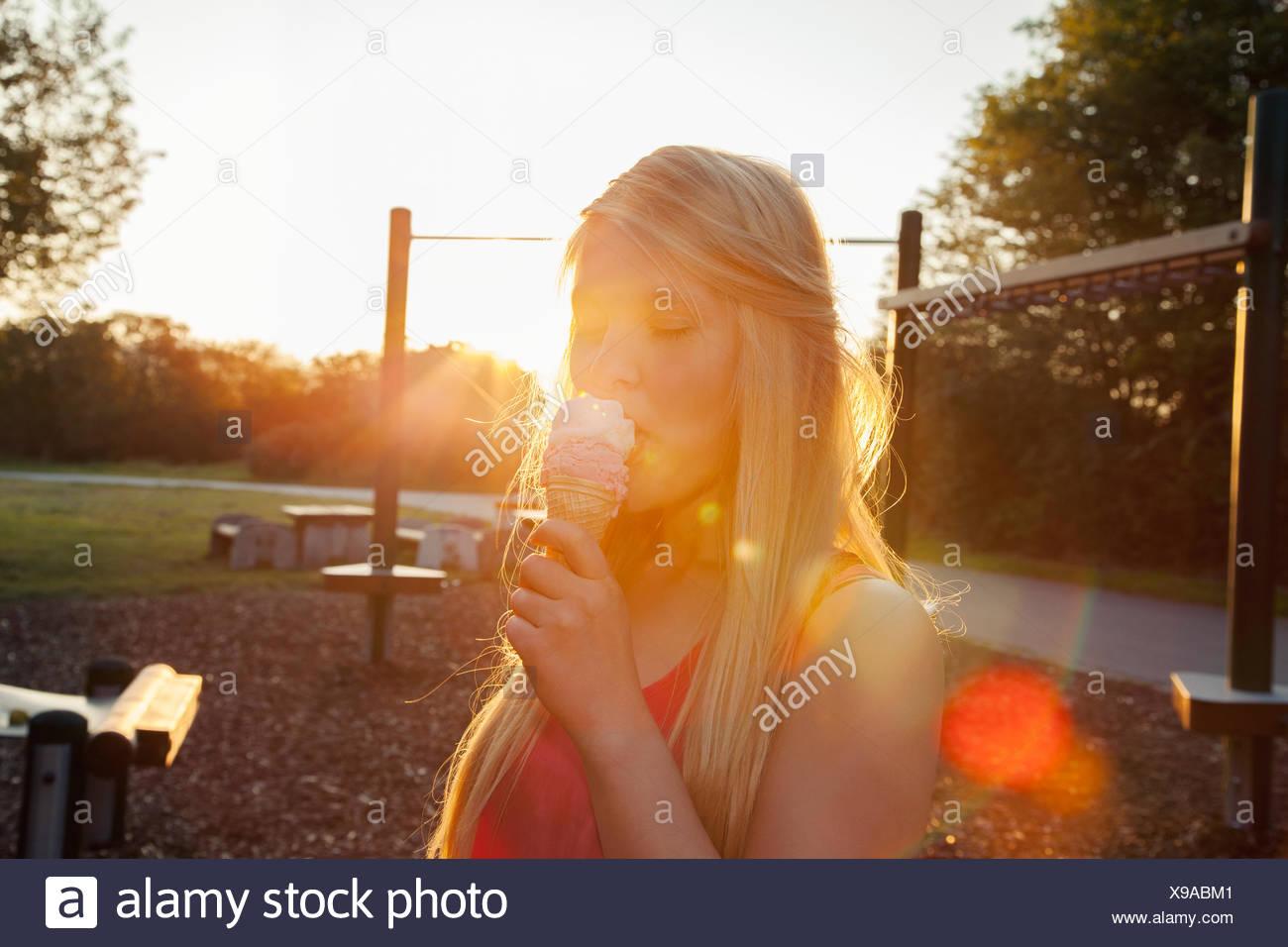 Junge Frau essen Eiscreme-Kegel im Park bei Sonnenuntergang Stockbild