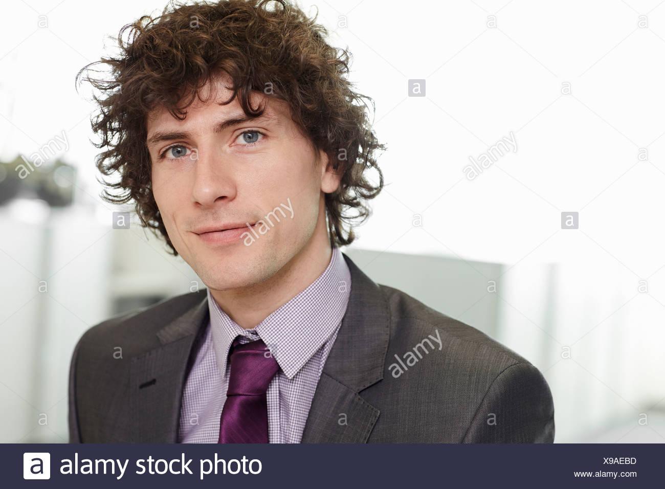 Porträt der Geschäftsmann mit dem lockigen Haar tragen Anzug und Krawatte Stockbild