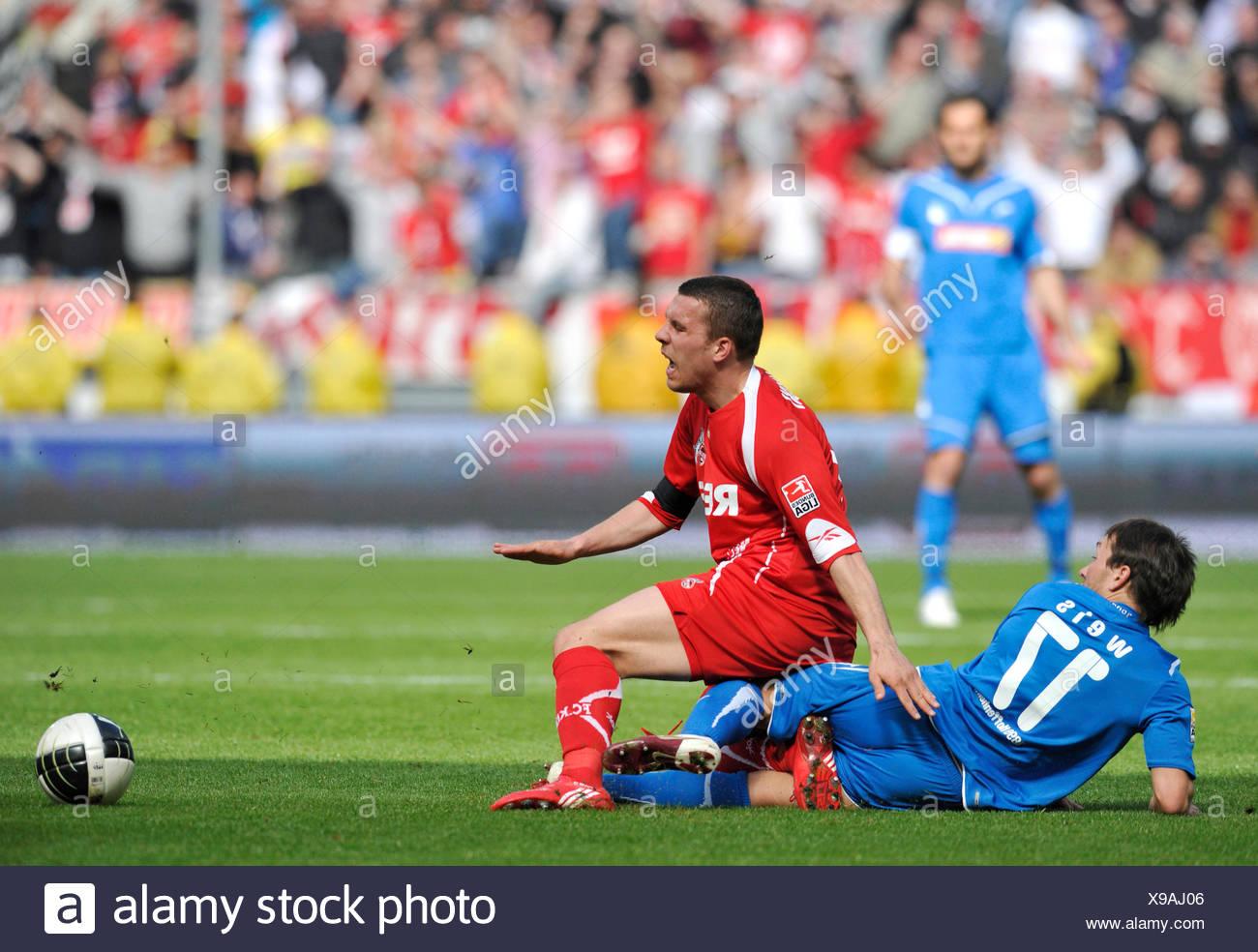 Begangenes Foul während Challenge, Tobias Weis der TSG 1899 Hoffenheim, links, Vs deutschen internationale Spieler Lukas Podolski 1. FC Stockbild
