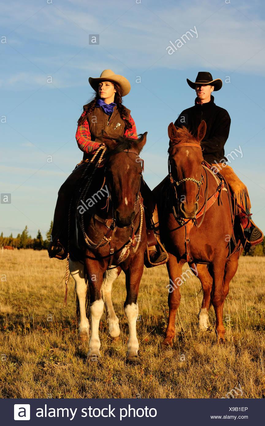 Cowboy und Cowgirl reiten Pferde, Blick in die Ferne, Saskatchewan, Kanada, Nordamerika Stockfoto