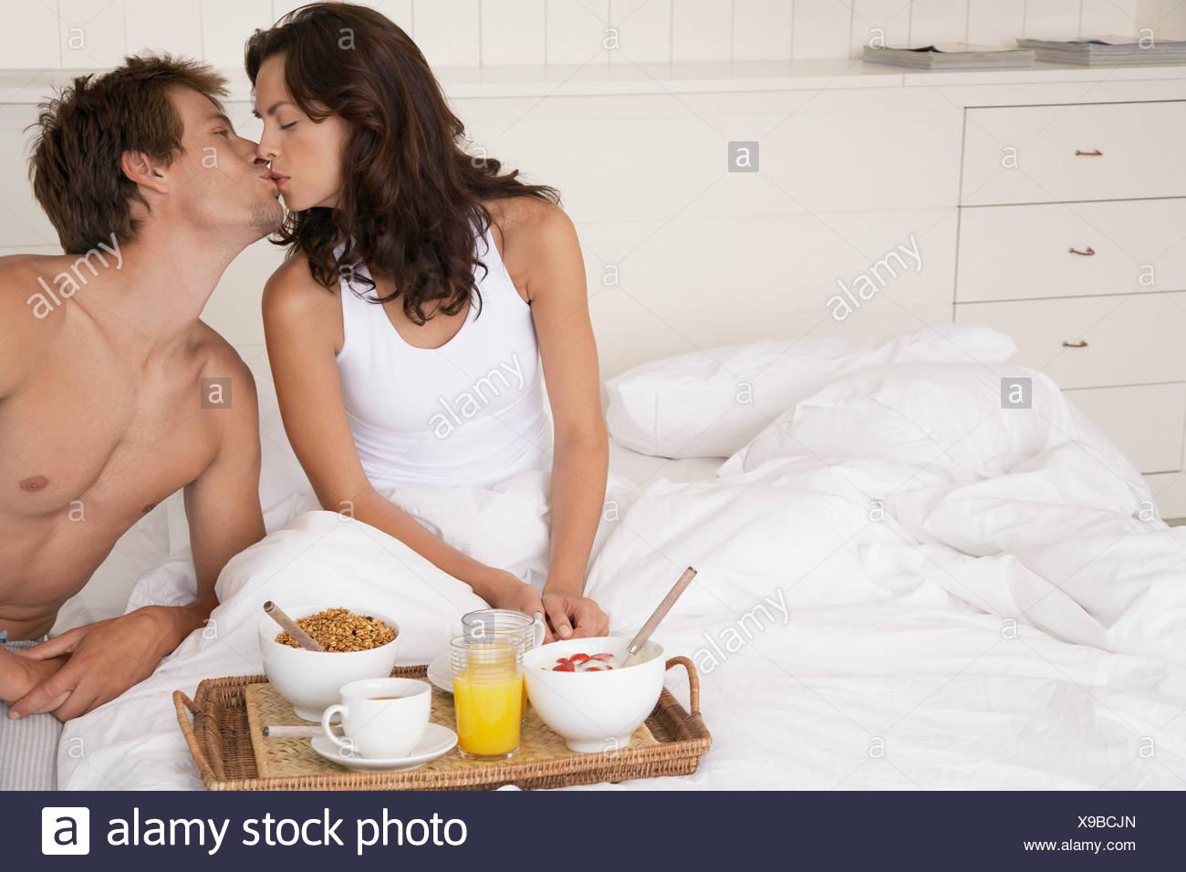 Paar küssen und frühstücken im Bett Stockfoto, Bild