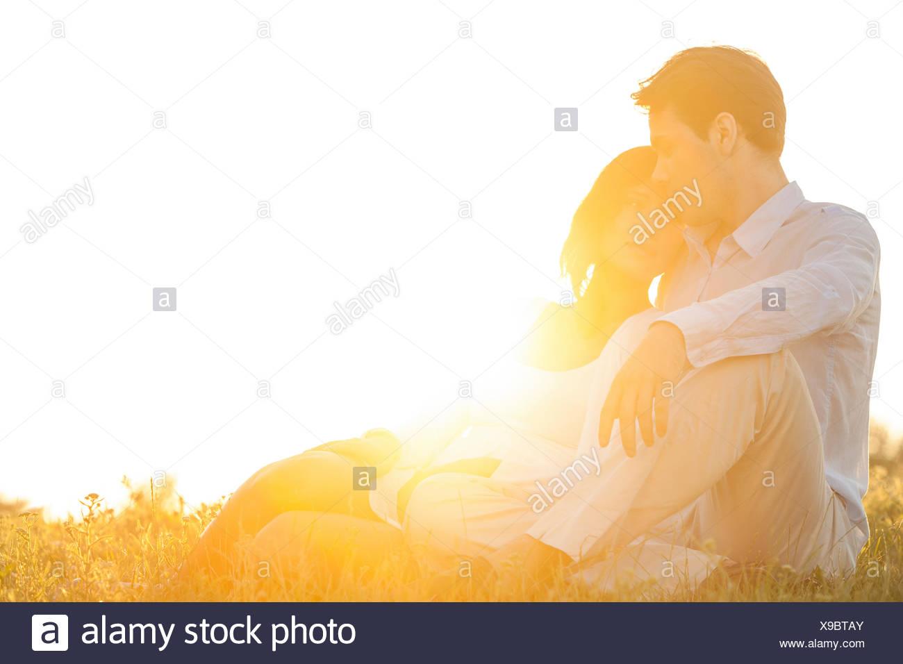 Junges Liebespaar sitzen auf dem Rasen im Park gegen den klaren Himmel Stockbild