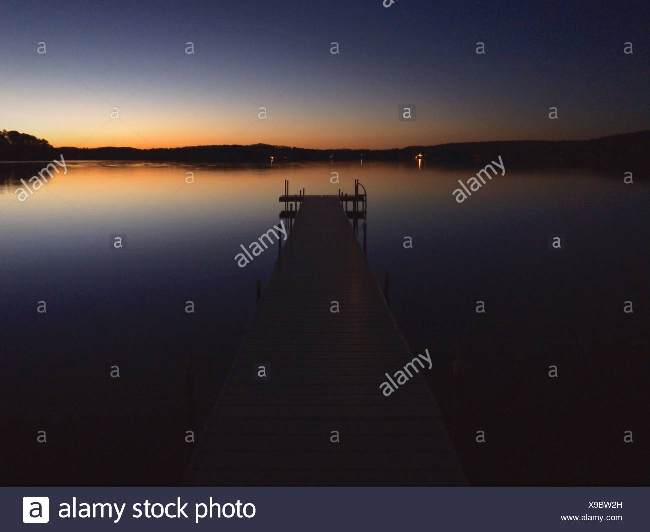 Pier mitten in See gegen klaren Himmel in der Abenddämmerung Stockbild