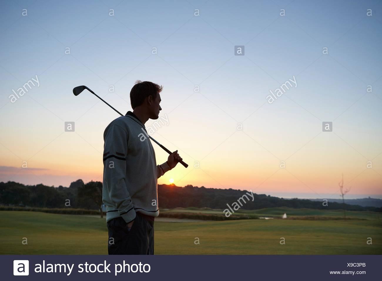 Golfer mit Golf Club über die Schulter schauen bei Sonnenuntergang Stockbild