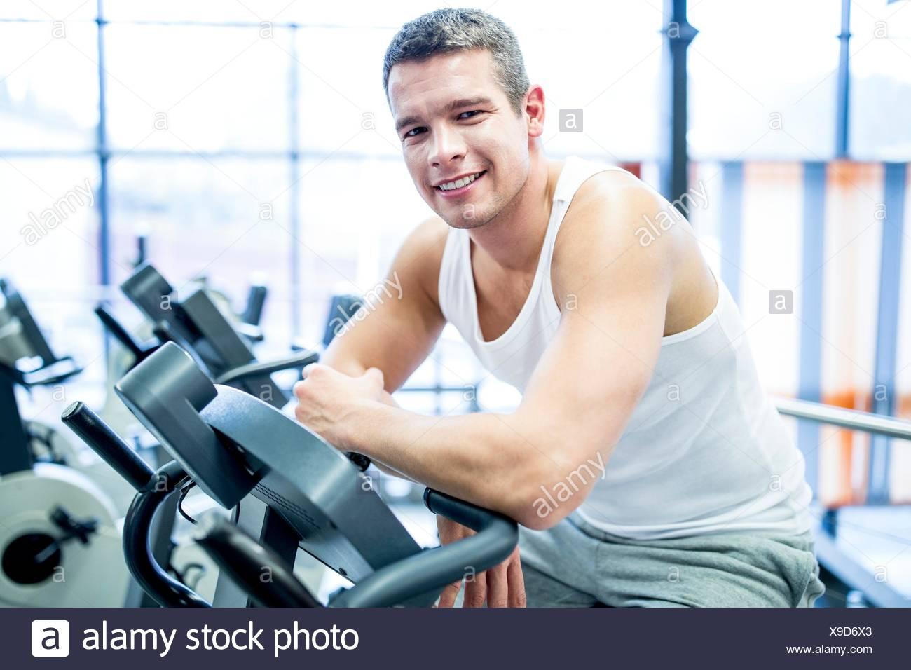 EIGENTUM FREIGEGEBEN. -MODELL VERÖFFENTLICHT. Porträt des jungen Mannes ruhen, während die Arbeit im Fitness-Studio, lächelnd. Stockbild