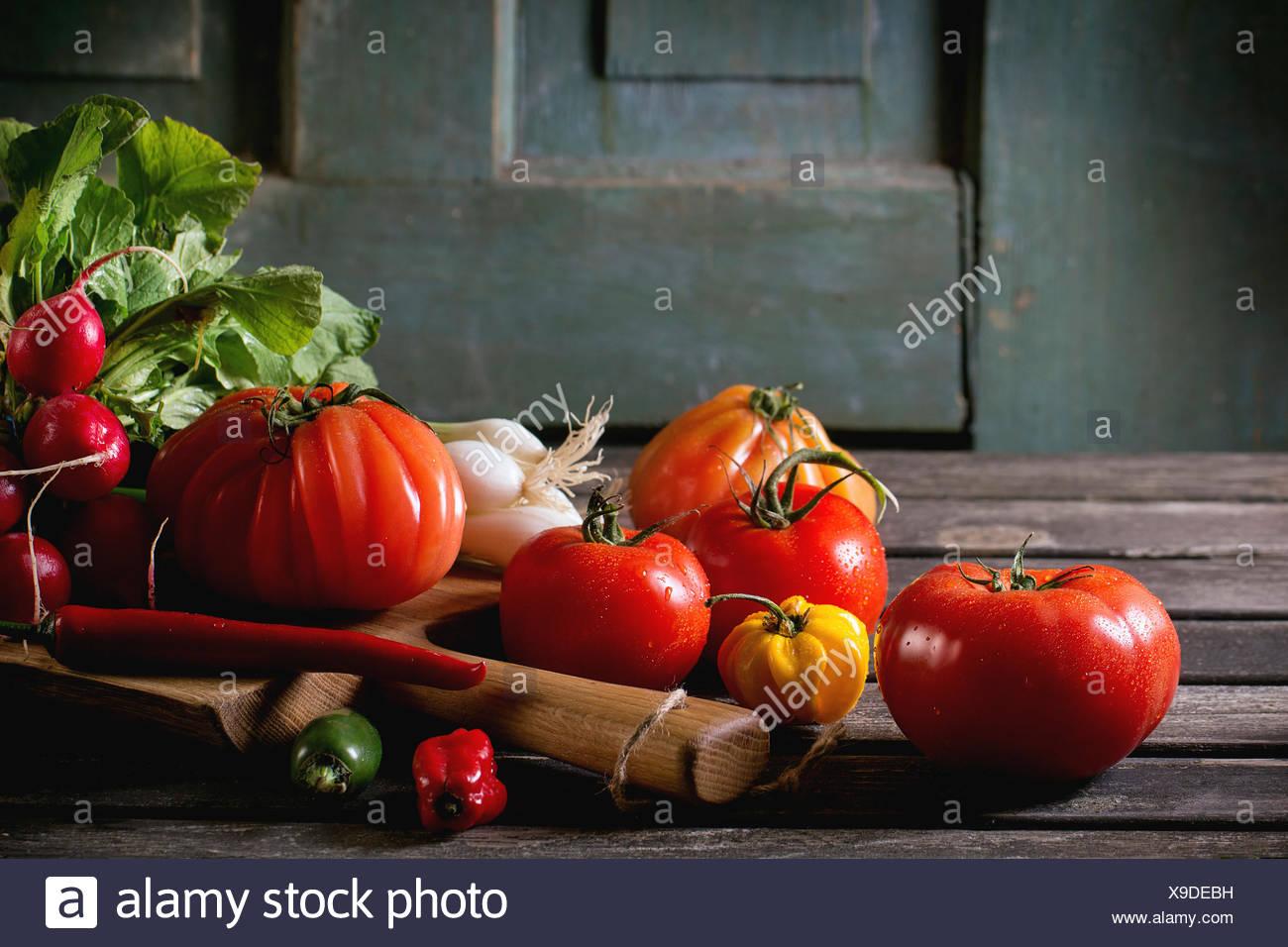 Haufen von Frischgemüse reif bunte Tomaten, Chilischoten, Frühlingszwiebeln und Bündel Radieschen auf Holz hacken an Bord über ol Stockbild
