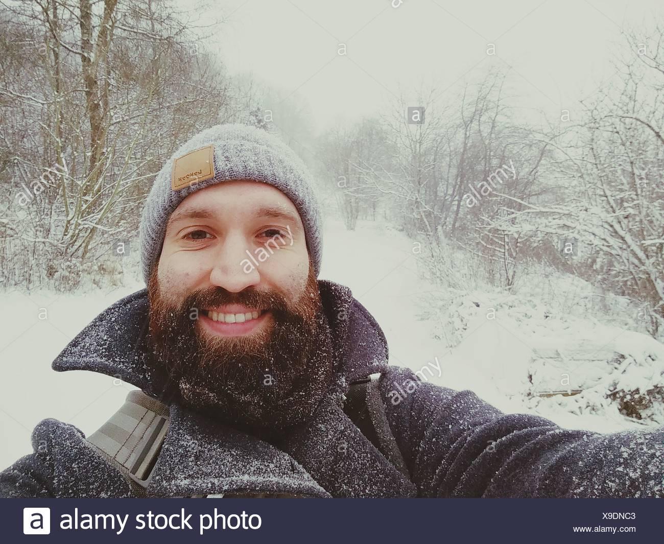 Porträt von einem fröhlichen jungen Mann im Schnee Stockbild