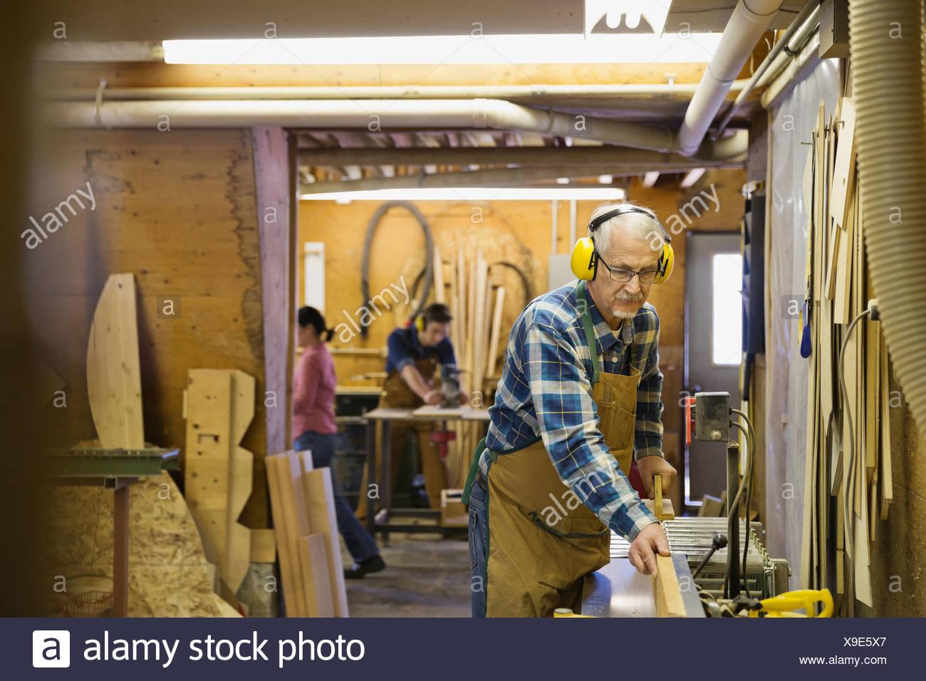 Senior mit Ausrüstung in Werkstatt Schreiner Stockbild