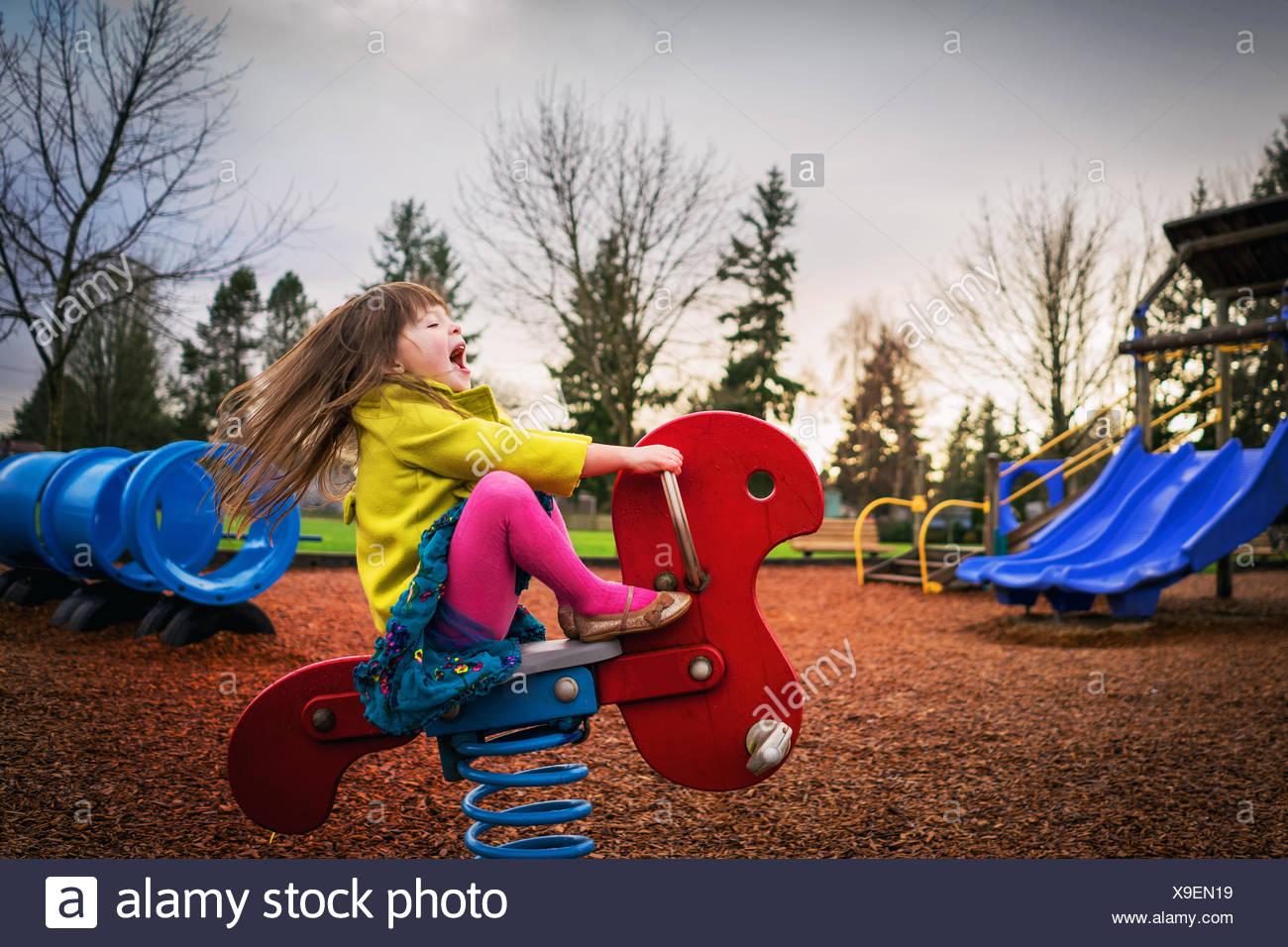 Mädchen sitzen auf Frühling reiten auf Spielplatz Stockfoto